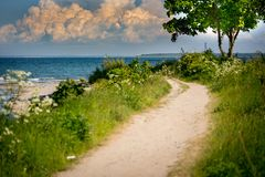 A narrow path leads to the beach from the sea stock image