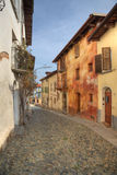 Narrow paved street among houses in Saluzzo. Stock Image