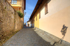Narrow paved street among houses in Saluzzo. Stock Photos