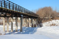 Narrow pedestrian bridge on stilts over the ravine in winter crossing the  river. Narrow pedestrian bridge on stilts over the ravine in winter crossing the stock photography