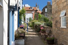 Narrow pedestrian lane and terraced houses in the village Robin Hoods Bay. Narrow pedestrian lane and terraced houses in the fishing English village Robin Hoods royalty free stock photo
