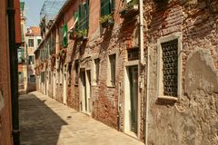 Narrow pedestrian street with houses made of red brick and flowers on the windows. Summer. Italy. Venice. Narrow pedestrian street with houses made of red brick Stock Photos