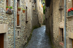 Narrow picturesque street of old Catalan town Stock Photos