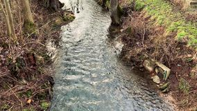 Narrow river flows in river bed stock footage