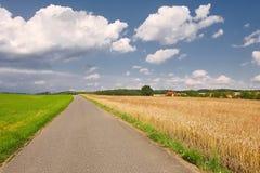 Road through farmlands. Narrow road through agricultural fields Stock Photos