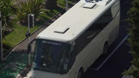 Narrow road with airport shuttles on their route, running from and to terminals stock footage
