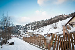 Narrow road covered by snow at countryside. Winter landscape with snowed trees, road and wooden fence. Cold winter day at village. Narrow road covered by snow at Stock Photo