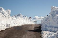 Deep snowbanks line a narrow road stock photography