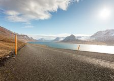 A narrow road next to a beautiful clean river. With amazing cloudy sky and snowy hills stock photos