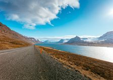 A narrow road next to a beautiful clean river. With amazing cloudy sky and snowy hills stock image