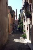 Narrow road between old damaged stone houses Stock Photos