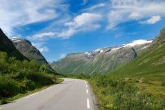 Narrow road running past green mountains. Royalty Free Stock Photo