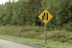 Narrow road sign post yellow black Quebec trans canada in front of forest. Narrow road sign post yellow black Quebec trans canada in front forest stock photos
