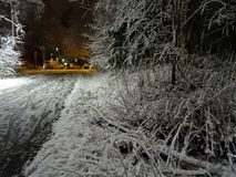 Narrow road under the lamp in autumn. First snow this year. In the evening, under the lamp, Nice view on the narrow walking way in autumn just beside the sea in Stock Photo
