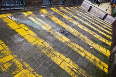 Narrow road with yellow stripes Stock Photos