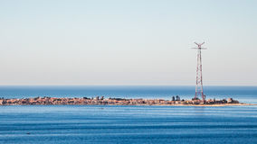 Narrow seashore with a city and tall antenna at the end. Narrow peninsula city surrounded with tranquil sea waters. At the end of the peninsula there is an Royalty Free Stock Photography