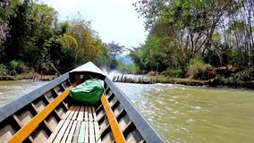Fast canoe trip along the canals of Inle Lake, Myanmar. The narrow seasonal creek in Inn Thein Indein village with wooden dams and lush forests on the banks is stock footage