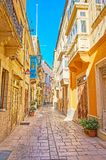 Shady streets of Birgu, Malta. The narrow shady Hilda Tabone street with old living buildings, decorated with colorful Maltese balconies and flowers in pots stock images
