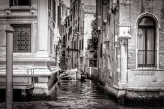 Narrow side street with a boat at Grand Canal, Venice. The narrow side street with a boat at Grand Canal in Venice, Italy. Vintage view of Venice canals in black Stock Images