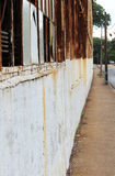 Narrow sidewalk beside derelict building Royalty Free Stock Photography