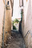 Narrow steep street with steps of ancient town stock images