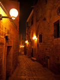 Narrow stone paved medieval street at night Royalty Free Stock Images