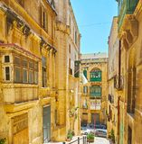 The stone city of Valletta, Malta. The narrow stone St Lucia street is quiet and empty on midday, Valletta, Malta Royalty Free Stock Photography