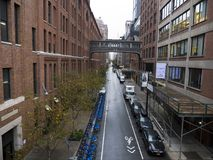 Narrow straight street with bridge. Connecting the two sides. Blue bike rental station Stock Photo