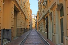 Narrow street. City street is too narrow that light cannot illuminate it. Typical european street in historical centers. Monaco Royalty Free Stock Photo