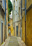 Narrow Street,  Aix-en-Provence, France. An older woman with white hair walks down a  quiet charming narrow street with mustard yellow color tones in historic Stock Image
