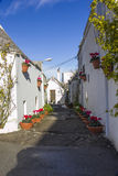Narrow street of Alberobello. Road flourished in the ancient district of Alberobello Royalty Free Stock Images