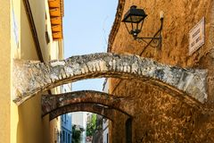 Narrow street with arch and lanterns in Spain. Narrow alley with old stone buildings in spanish city of Malgrat de Mar. Decorative curved arch over medieval Royalty Free Stock Image