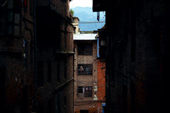 Narrow street Bhaktapur. Clearance at the end of a narrow dark streets of Bhaktapur with views of the Himalayan Mountains Stock Photo