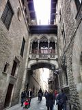 Narrow street Carrer del Bisbe in gothic quarter, Barcelona, Spain Royalty Free Stock Images