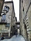 Narrow street Carrer del Bisbe in gothic quarter, Barcelona, Spain Stock Images