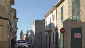Narrow street with cars of old town. Art. Beautiful narrow street with old stone bell tower on background of sleeping stock video footage