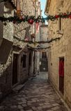Narrow street with Christmas decorations in Old Town, Kotor royalty free stock images