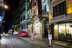 Narrow street of city, hotel and parked cars stock photography