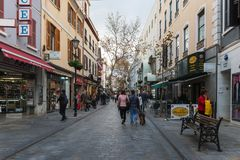 Narrow street of the city with small shops and walking people. GIBRALTAR, EUROPE - DECEMBER 2017: Narrow street of the city with small shops and walking people Royalty Free Stock Photo