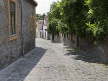 Narrow street with coble stone pavement Stock Images