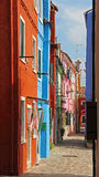 Narrow street with colorful apartment houses in Burano, Venice, Italy Royalty Free Stock Photo