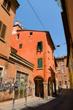 Narrow street with colourful facades and wooden window shutters in Bologna, Italy Stock Image