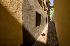 Narrow street with contrasting shadows from the sun Royalty Free Stock Photo
