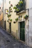Narrow street and the facade of a building with flowers in the traditional neighborhood of Alfama in Lisbon, Portugal. Concept for visit Lisbon royalty free stock image