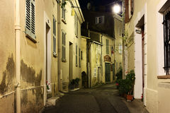 Narrow street with flowers in the old town Mougins in France. Ni. MOUGINS, FRANCE - OCTOBER 31, 2014: Narrow street with flowers in the old town at night Stock Photos