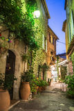 Narrow street with flowers in the old town Mougins in France. Ni. Ght view Royalty Free Stock Photo