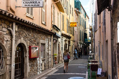 Narrow street with a girl walking. Woman walking on a narrow commercial street in Antibes, France Stock Photo