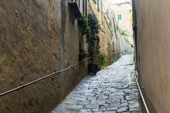 Narrow street going up in a town from Tuscany Stock Image
