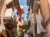 Narrow street with hanging clothes on balconies in south of Italy, Bari. Drying laundry on balcony. Italian southern architecture. royalty free stock image