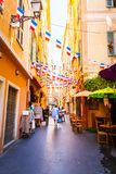 Narrow street with hanging France flags in old part of Nice. Royalty Free Stock Images